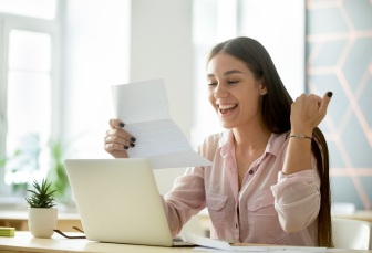 Happy young woman excited by reading good news in letter